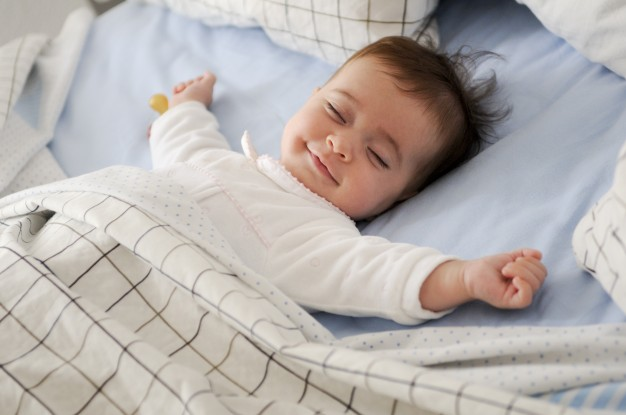 smiling-baby-lying-on-a-bed_1139-14